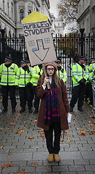 © Licensed to London News Pictures. 04/11/2015. London, UK. A student stands at the gates of Downing Street carring a placard saying that she is homeless. Thousands of students held a protest in central London over fees and cuts. Photo credit: Peter Macdiarmid/LNP