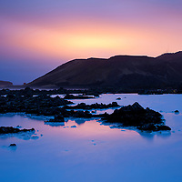 Iceland, Reykjanes Peninsula, Grindavik, Glow of city lights above mountains surrounding Blue Lagoon at night on spring evening
