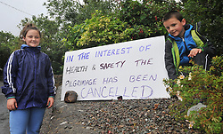 Claudia and Luke Dempsey from Co Clare stand by the cancellation notice for pilgrims arriving at Croagh Patrick on reek sunday.<br /> Pic Conor McKeown