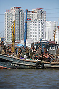 North Koreans use a fishing boat as a ferry on the Yalu River, with the Chinese town of Dandong in the background.  DPRK, north korea, china, dandong, border, liaoning, democratic, people's, rebiblic, of, korea, nuclear, test, rice, japan, arms, race, weapons, stalinist, communist, kin jong il