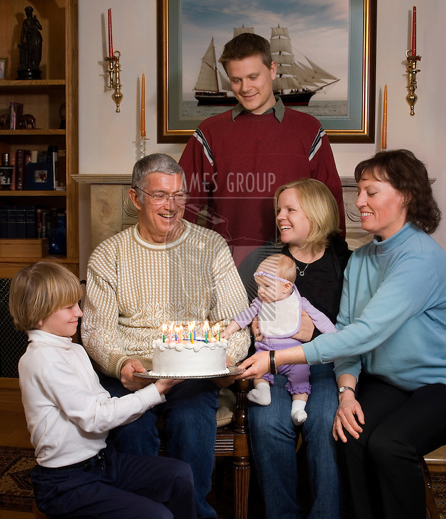 Grandfather receiving birthday cake with grandmother, children and grandchildren