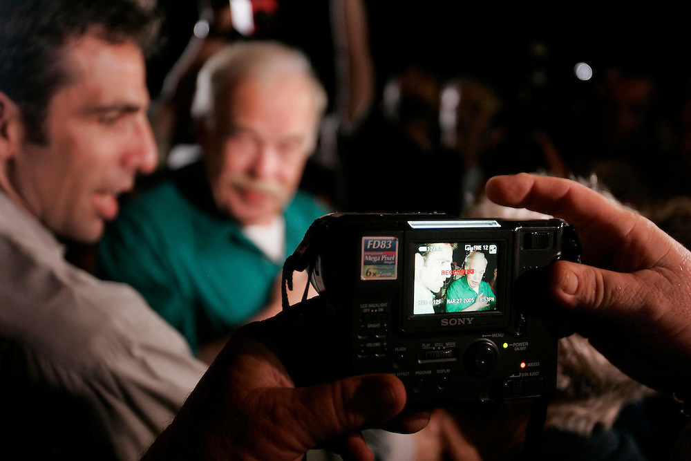 A protester reviews of photo he has just taken of Bob Shindler Jr (L) and his father Bob Schindler (R) outside the Woodside Hospice where the brain damaged daughter Terri Schiavo remained without a feeding tube  in Pinellas Park, Florida on March 27, 2005. REUTERS/Scott Audette