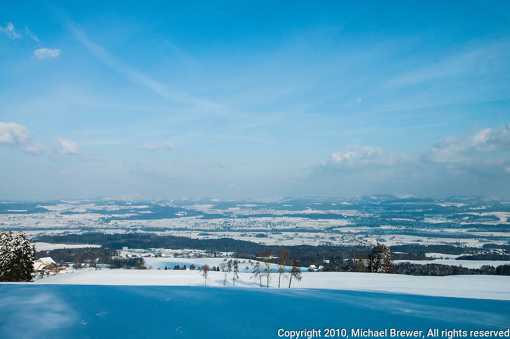 Looking out over the countryside of the Reusstal from the hills above Muri on a snowy day, Aargau, Switzerland.
