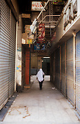 Woman walking down laneway, Cairo, Egypt.