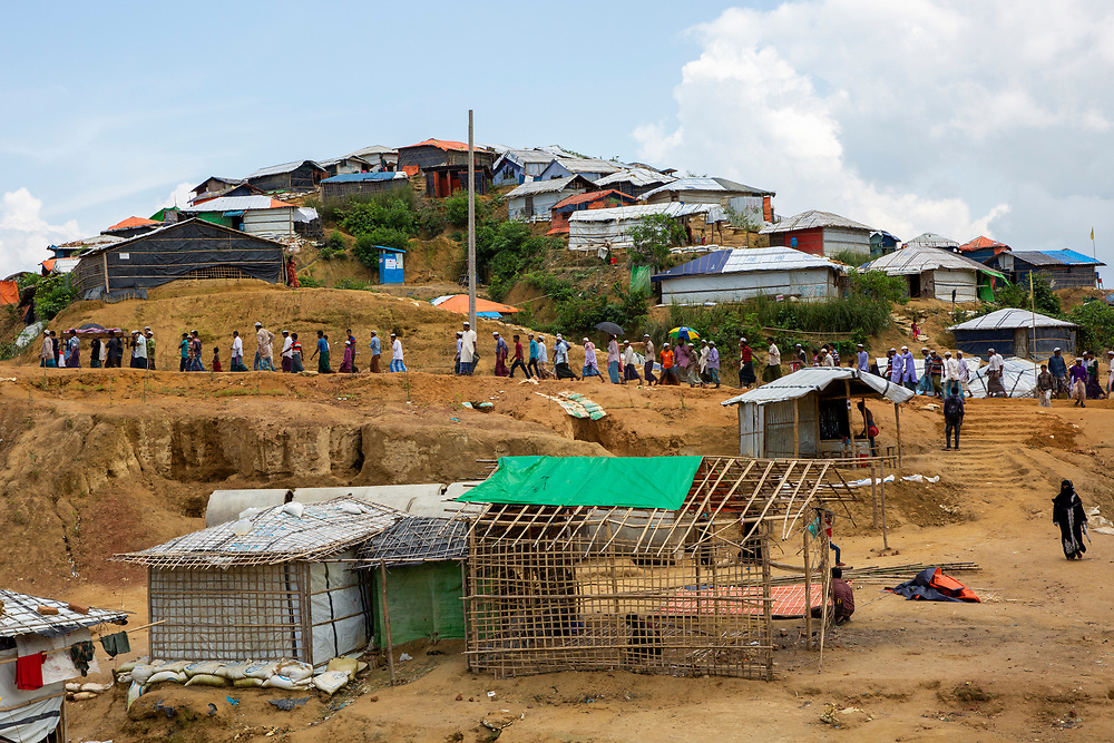 Men walk along the dirt path as part of a funeral procession within the Kutupalong refugee camp outside Cox Bazar, Chittagong Division, Bangladesh, Asia. The rapid influx of the Rohingya people into the refugee camp has led it to be called the largest slum in the world.  (photo by Andrew Aitchison / In pictures via Getty Images)