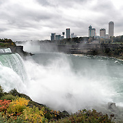 The American Falls (at left) at Niagara Falls on the Niagara River on the border between the United States and Canada. In the distance, just to the left of the buildings, are the larger Horseshoe Falls (or Canadian Falls).