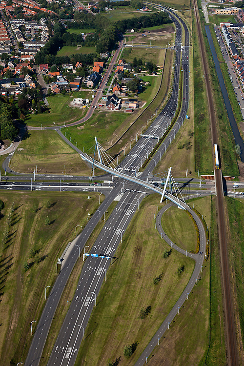 Nederland, Overijssel, Zwolle, 03-10-2010; Tuibrug voor fietspad kruist kruispunt van lokale wegen. Rechts de spoorlijn Kampen-Zwolle, met dieseltrein. Het lokale lijntje wordt vervangen door de Hanzelijn..Cable-stayed bridge with bike path crosses the intersection of local roads. Right: the railroad Zwolle Kampen, with diesel. The local line will be replaced by the Hanzelijn..luchtfoto (toeslag), aerial photo (additional fee required).foto/photo Siebe Swart