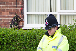 © Licensed to London News Pictures . 13/11/2012 . Manchester , UK . Police outside the family home of British soldier , Drummer Lee Rigby of the 2nd Battalion Royal Regiment of Fusiliers , in Middleton . A single poppy and army fatigues hang on the wall outside the front door . Drummer Rigby was murdered in Woolwich yesterday (Wednesday 23rd May) . Photo credit : Joel Goodman/LNP
