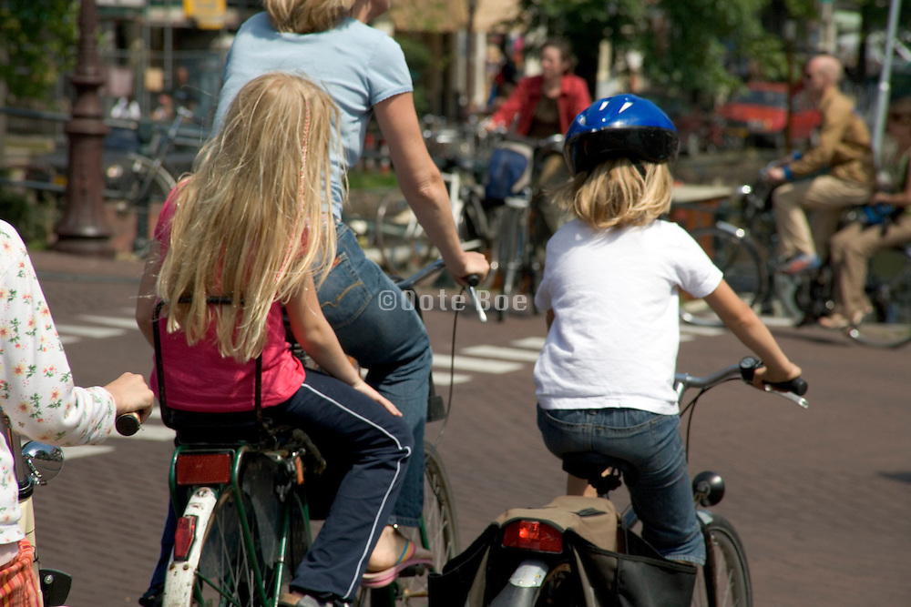 mother cycling with her two children through the city Amsterdam