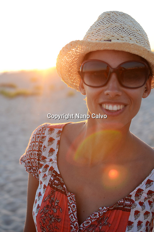 Young woman with straw hat on the beach at sunset