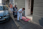As others try to squeeze through a space on the narrow pavement, a hotel employee cleans the matt in front of the Hotel do Norte, on 20th July, in Porto, Portugal. Scrubbing the step and the matt which contain the name of this establishment, the cleaner takes up most of the space on the sidewalk. (Photo by Richard Baker / In Pictures via Getty Images)
