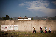Locals walk past a wall encompassing the perimeter of the compound where Osama Bin Laden was reportedly killed in an operation by US Navy Seals, on May 3, 2011, in Abottabad, Pakistan.  The operation, code-named Operation Neptune Spear, was launched from neighbouring Afghanistan by Seal Team Six. U.S. forces took bin Laden's body to Afghanistan for identification, then dumped it the Arabian Sea. Pakistan has since been widely suspected as having prior knowledge of his whereabouts as the compound was less than a kilometre from the country's biggest military academy. Osama bin Laden was allegedly responsible for supporting the bombing of the US Embassy in Nairobi, Kenya, the attack on the USS Cole and the suicidal attacks of September 11, 2001 in the US. (Photo by Warrick Page)