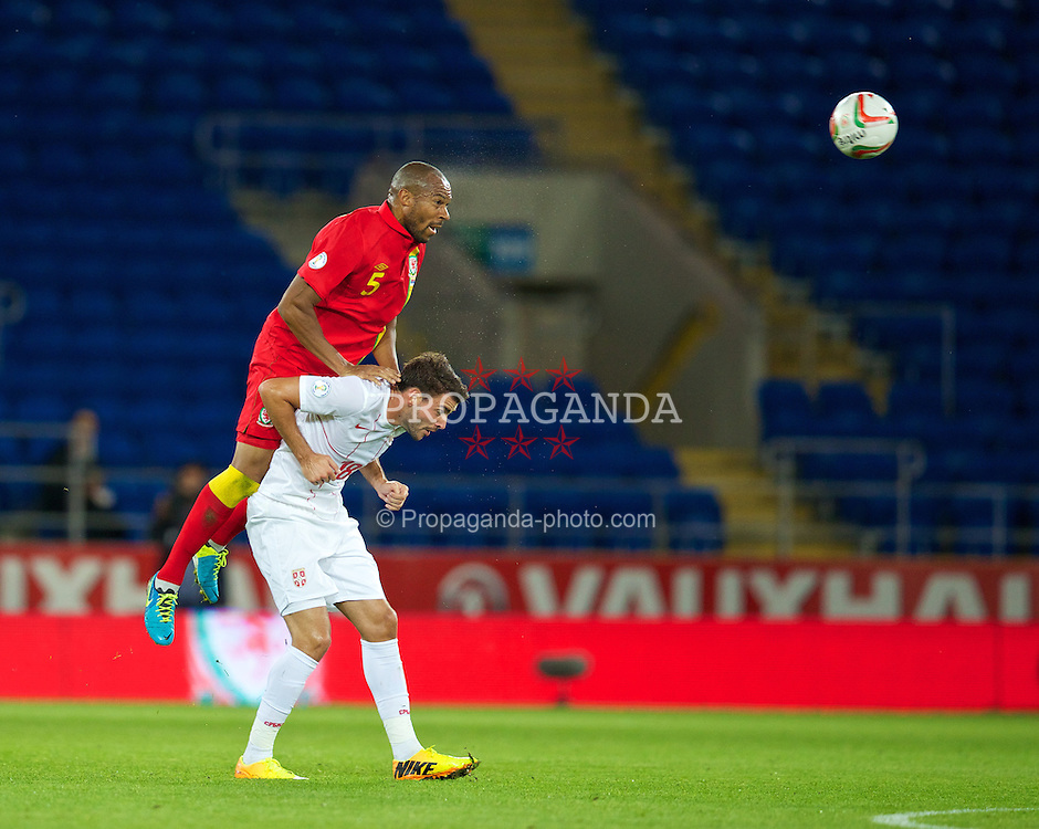 CARDIFF, WALES - Tuesday, September 10, 2013: Wales' Daniel Gabbidon in action against Serbia's Filip Djordjevic during the 2014 FIFA World Cup Brazil Qualifying Group A match at the Cardiff CIty Stadium. (Pic by David Rawcliffe/Propaganda)