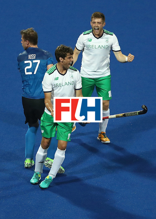 RIO DE JANEIRO, BRAZIL - AUGUST 12:  Shane O'Donoghue #16 and John Jermyn #11 of Ireland react to scoring a goal as Lucas Rossi #27 of Argentina looks on during a Men's Preliminary Pool A match on Day 7 of the Rio 2016 Olympic Games at the Olympic Hockey Centre on August 12, 2016 in Rio de Janeiro, Brazil.  (Photo by Sean M. Haffey/Getty Images)