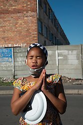 """A young prays, holding her plate, in Parkwood, Cape Town, South Africa, on Sunday, May 31, 2020. The joint prayer in Afrikaans opened a special chicken lunch served by the Parkwood Community Upliftment (PCU) project. The youth organization, which normally feeds children as part of an after-school care program, has been feeding children, the elderly, and many other hungry people, in this poverty-stricken area in the Cape Flats since lockdown started more than two months ago. As the nation moves down to Level 3, on June 1st, CPU founder Max Amansure says the organization will continue to feed people. Often it's """"only"""" bread as the organization doesn't have any regular funding. However, as the area has been hard hit by COVID-19, Amansure says he wishes Parkwood could have remained on Level 5 Lockdown. PHOTO: EVA-LOTTA JANSSON"""