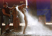 """""""Bobcat"""" showers off backstage after wrestling with another woman in chocolate sauce at the Harley-Davison anniversary party in Milwaukee August 29, 2003. The legendary American motorcycle company is celebrating its 100th anniversary and is expected to draw 200,000 to 300,000 people to the companies home base over four days.    REUTERS/Rick Wilking"""