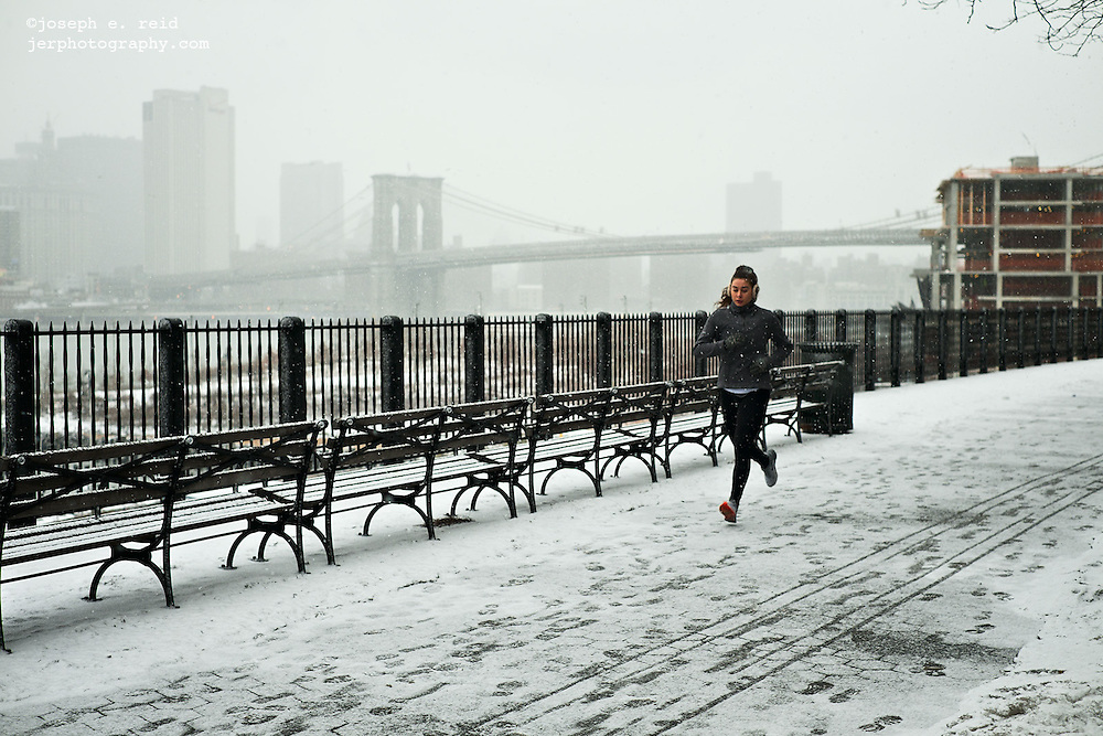 Woman jogging in snow on Brooklyn Heights Promenade, Brooklyn, NY, US