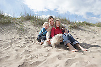 Parents with daughter (5-6) and dog on beach portrait