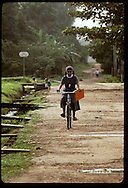 Nun rides her bicycle down dirt road in town of Eirunepe, state of Amazonas. Brazil