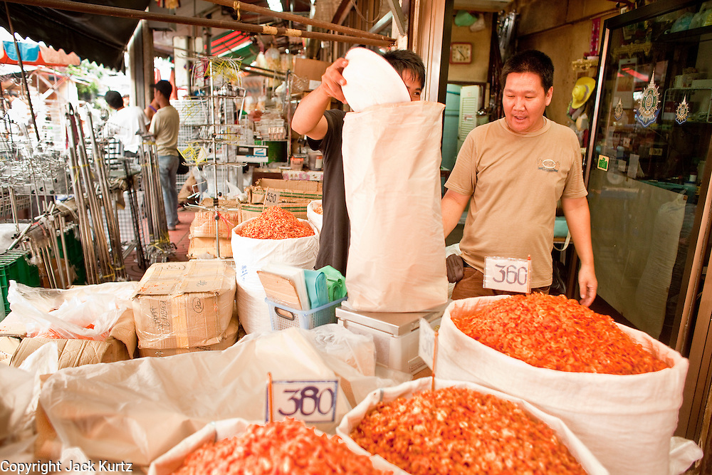 07 OCTOBER 2009 -- BANGKOK, THAILAND: Men package dried shrimp in their market stall in Chinatown in Bangkok, Thailand. Chinatown is the old commercial heart of Bangkok with thousands of small shops selling everything from clothes to dried fish to case lots of shoes and gem stones.   Photo By Jack Kurtz