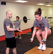 (from left) Owner Jason Hoskins of Dayton, Kristen Pertner of Dayton and  Alyssa Medeiros of Beavercreek during a workout of the day session at Vigor Crossfit in Moraine, Wednesday, January 25, 2012.