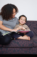 Mother reading book with son (5-6) on sofa