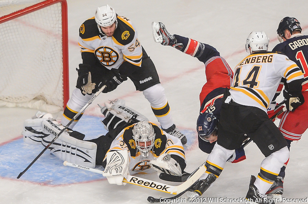 Boston Bruins goalie Tim Thomas (30) dives to clear a loose puck away from New York Rangers center Derek Stepan (21) during first period NHL action between the New York Rangers and the Boston Bruins at Madison Square Garden in New York, N.Y.