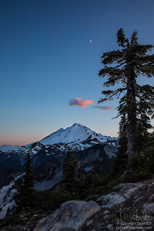 A crescent moon is high in the sky over Mount Baker in Washington's North Cascades at dusk. Mount Baker, at 10,781 feet (3,286 meters), is the third largest volcano in Washington state and last erupted in 1880.