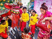 """19 FEBRUARY 2015 - BANGKOK, THAILAND:  Dragon dancers wait for a woman to get money for a donation out of her purse during a Chinese New Year parade on Yaowarat Road in Bangkok. 2015 is the Year of Goat in the Chinese zodiac. The Goat is the eighth sign in Chinese astrology and """"8"""" is considered to be a lucky number. It symbolizes wisdom, fortune and prosperity. Ethnic Chinese make up nearly 15% of the Thai population. Chinese New Year (also called Tet or Lunar New Year) is widely celebrated in Thailand, especially in urban areas that have large Chinese populations.   PHOTO BY JACK KURTZ"""