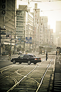 A taxi crosses streetcar tram tracks in downtown Hiroshima, Japan.  Light rail tracks form the backbone of the public transportation system in the city of Hiroshima.