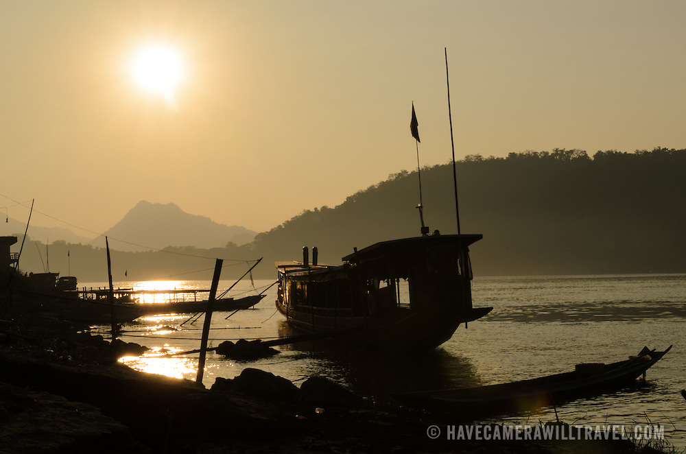 A wooden, covered sampan is silhouetted against the setting sun on the Mekong River near Luang Prabang in central Laos.