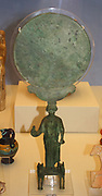 Caryatid Mirror. Corinth was famous for its metal workshops producing luxury items. This disc mirror, supported by a female figure (caryatid), would have been polished and reflective.  The woman stands on a base flanked by two figures of Pegasus and holds a bird in her right hand.  Made in Corinth about 460 BC
