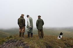 © Licensed to London News Pictures. 13/08/2016. Swinithwaite, UK. Three men look across the misty moor during a grouse shoot in high on the Yorkshire moors in Swinithwaite, North Yorkshire. Yesterday was the glorious 12, the day that traditionally marks the start of the grouse shooting season. Photo credit : Ian Hinchliffe/LNP