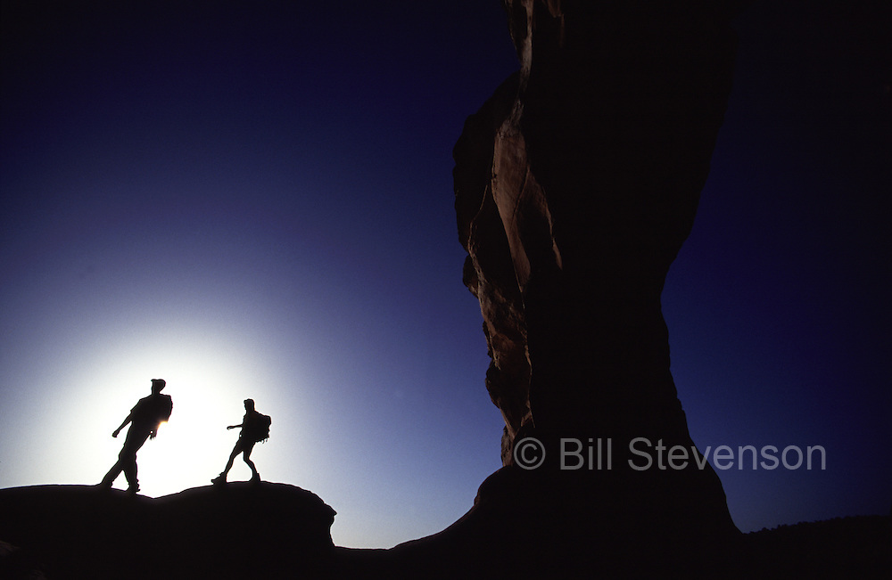 A picture of a silhouette of a couple hiking under an arch in Arches National Park, UT.