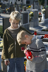 Children at the cemetery lighting a candle.  (Photo by: Vid Ponikvar / Sportal Images).