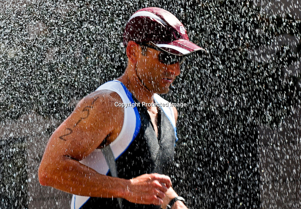Ernesto Carol from Harbor City, California runs through a spray of water from a fire hydrant as he runs down Grand Ave. in Downtown L.A. during the Los Angeles Triathlon.