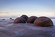 spherical beach boulders (concretions) surrounded by the swirling water in the dusky light at koekohe, moeraki, south island, new zealand