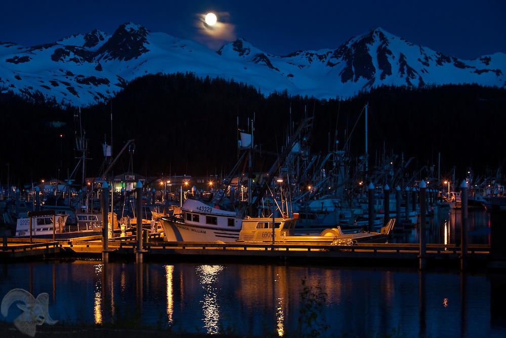 A full moon rises over the Heney Range and the Cordova, Alaska Harbor. The larger vessel , Prince William, in the foreground is a purse-seiner and the smaller is a drift gillnet boat. Cordova is located on the eastern shore of Prince William Sound near the mouth of the Copper River, which spills into the Gulf of Alaska.