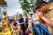12 APRIL 2013 - BANGKOK, THAILAND:  A Thai man prays after sprinkling scented oils on the Phra Buddha Sihing on the first day of Songkran in Bangkok. The Phra Buddha Sihing, a revered statue of the Buddha, is carried by truck through the streets of Bangkok so people can make offerings and bathe it in scented oils. Songkran is celebrated in Thailand as the traditional New Year's Day from 13 to 16 April. The date of the festival was originally set by astrological calculation, but it is now fixed. If the days fall on a weekend, the missed days are taken on the weekdays immediately following. Songkran is in the hottest time of the year in Thailand, at the end of the dry season and provides an excuse for people to cool off in friendly water fights that take place throughout the country. The traditional Thai New Year has been a national holiday since 1940, when Thailand moved the first day of the year to January 1. The first day of the holiday period is generally the most devout and many people go to temples to make merit and offer prayers for the new year. .  PHOTO BY JACK KURTZ