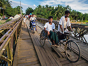 05 NOVEMBER 2014 - SITTWE, RAKHINE, MYANMAR: Rohingya Muslims cross a bridge into a Rohingya Muslim IDP camp near Sittwe. After sectarian violence devastated Rohingya communities and left hundreds of Rohingya dead in 2012, the government of Myanmar forced more than 140,000 Rohingya Muslims who used to live in and around Sittwe, Myanmar, into squalid Internal Displaced Persons camps. The government says the Rohingya are not Burmese citizens, that they are illegal immigrants from Bangladesh. The Bangladesh government says the Rohingya are Burmese and the Rohingya insist that they have lived in Burma for generations. The camps are about 20 minutes from Sittwe but the Rohingya who live in the camps are not allowed to leave without government permission. They are not allowed to work outside the camps, they are not allowed to go to Sittwe to use the hospital, go to school or do business. The camps have no electricity. Water is delivered through community wells. There are small schools funded by NOGs in the camps and a few private clinics but medical care is costly and not reliable.   PHOTO BY JACK KURTZ
