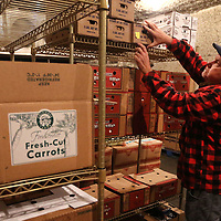 Robert McKissack, warehouse manager at Cockrell Banana, checks the produce of pre-cut items in one of the many coolers in the warehouse at Cockrell Banana in Tupelo. The produce supply company sees a pick up in business during the holidays.