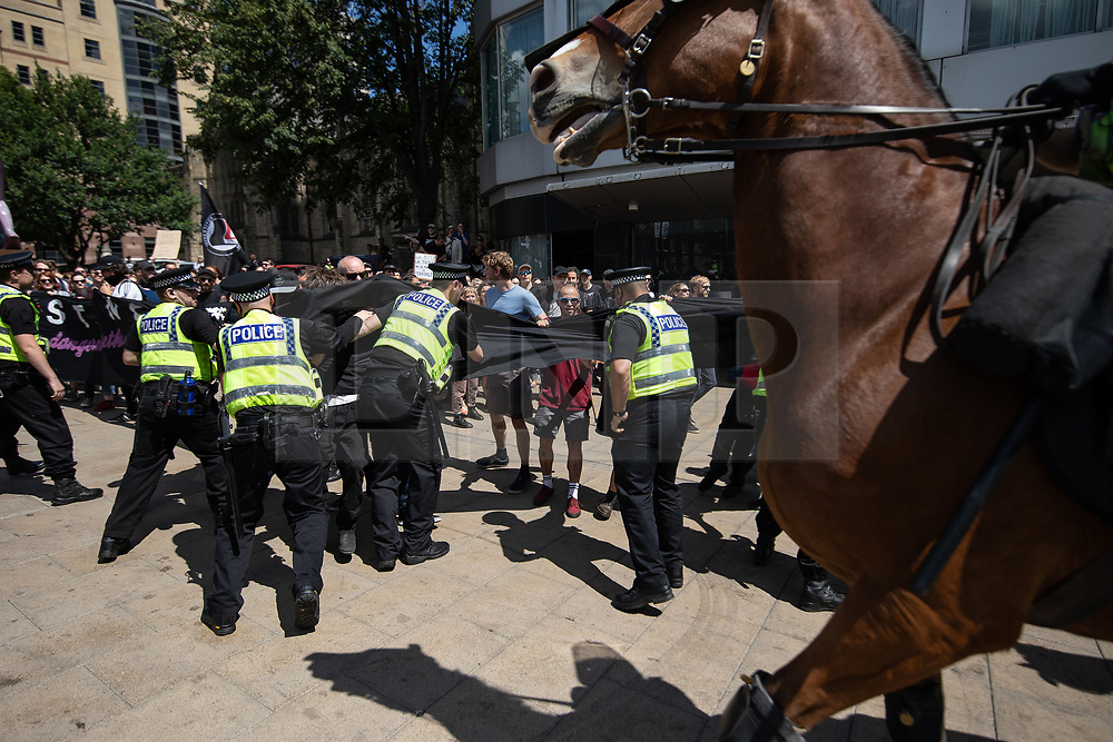 """© Licensed to London News Pictures . 07/07/2018 . Leeds , UK . Police clash with anti-fascist counter demonstrators attempting to block the path of an anti-Islam march by supporters of jailed EDL founder Tommy Robinson , which includes those from the """" Yorkshire Patriots """" and """" First for Britain """" , in Leeds City Centre . Robinson ( real name Stephen Yaxley-Lennon ) was convicted of Contempt of Court in May 2018 after committing a second offence , whilst serving a suspended sentence for the same crime . Photo credit : Joel Goodman/LNP"""