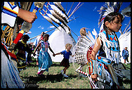 Little blond girl dances with Assiniboine and Gros Ventre Indians from Fort Belknap Reservation during Lewis and Clark Festival; Great Falls, Montana