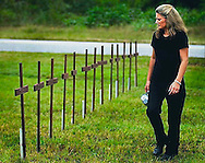 Beki Blevins walks past 13 wooden crosses erected in front of  West Brookwood Church in Brookwood, Ala., Sept. 22, 2003, as part of a memorial for the miners killed at nearby Jim Walters Mine No. 5 in 2001. Blevins' father-in-law, David Blevins, was one of 13 miners who died that day. (Photo by Carmen K. Sisson/Cloudybright)