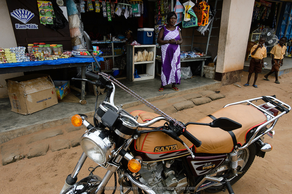 Through her participation in a 'Banking on Change' Village Savings and Loan Association (VSLA), Vincentia Dei-Zanga was able to purchase a motorcycle which she hires out as an 'okada', or motorcycle taxi. She is pictured in front of her store in Asiekpe in the Volta Region of Ghana on 12 September 2012.