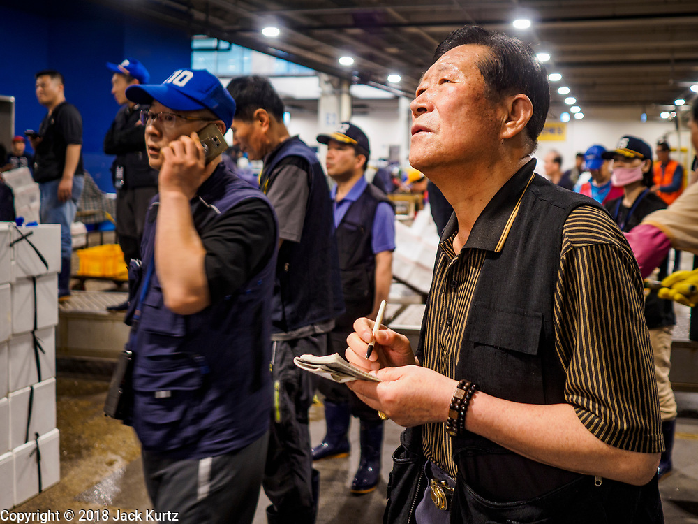 07 JUNE 2018 - SEOUL, SOUTH KOREA:  A fish buyer takes notes during the wholesale fish auction in the Noryangjin Fish Market. The auctions start about 01.00 AM and last until 05.00 AM. Noryangjin Fish Market is the largest fish market in Seoul and has been in operation since 1927. It opened in the current location in 1971 and was renovated in 2015. The market serves both retail and wholesale customers and has become a tourist attraction in recent years.     PHOTO BY JACK KURTZ