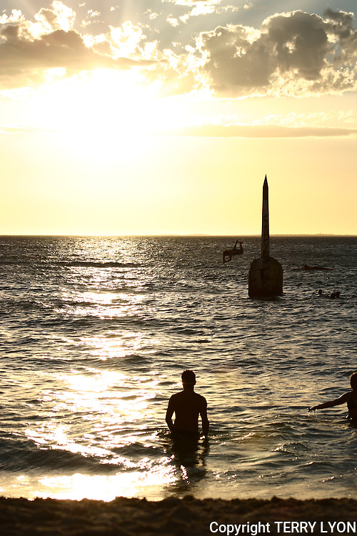 A golden Cottesloe beach sunset with swimmers and a boy diving off the pylon.