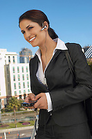 Businesswoman wearing headset, text messaging, outdoors