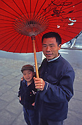 On a sidewalk in Guilin, China, a Chinese father and son stand under red umbrella