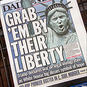 Humorous political  Newpaper cover headlines about  President Trump newest actions.<br /> <br /> Daily News headline &quot;Grad'Em By Their Liberty&quot; &quot;Trump declares war on legal immigration as White House disses symbol of hope&quot;
